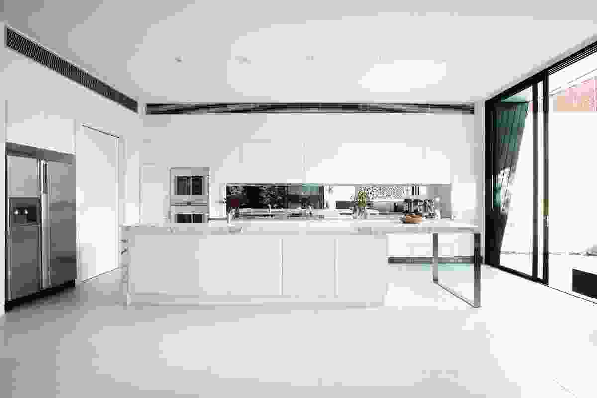 The kitchen is adjacent to the central garden, granting it ample natural light.