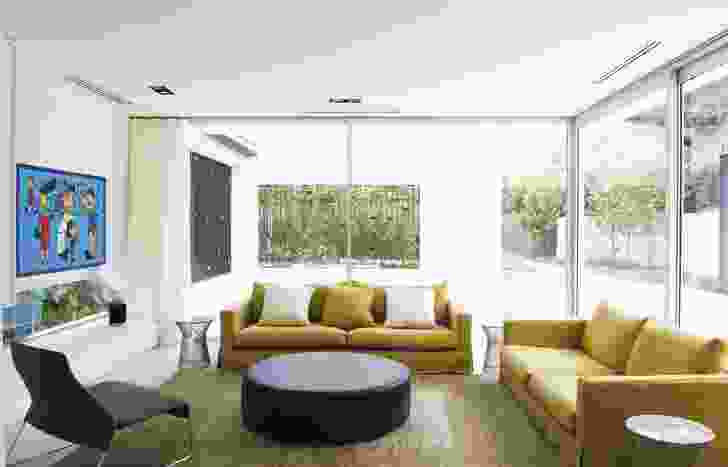 "The living room looks out onto the outdoor pool ""room"" and beyond into the garden."