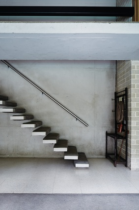 Concrete stair treads cantilever from the wall in place of a conventional stair.