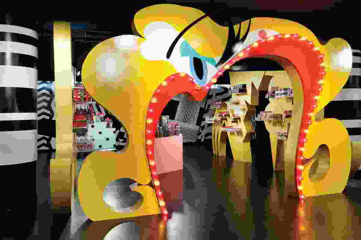 An arch featuring lady gaga's scarlet lips leads into a candy shop selling branded merchandise.