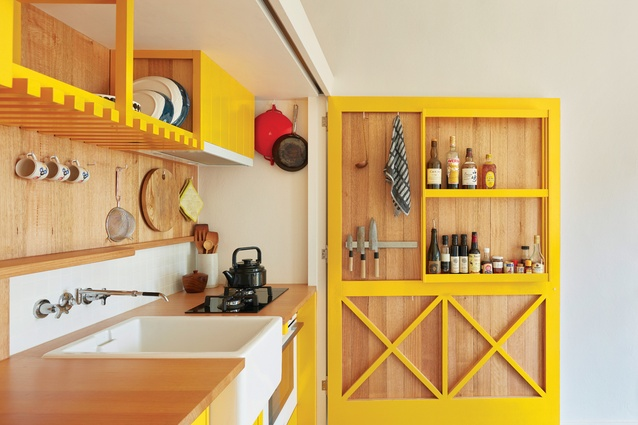 "A large hinged door doubles as a pantry in a kitchen that ""opens up, hides away, slides along and folds out."""