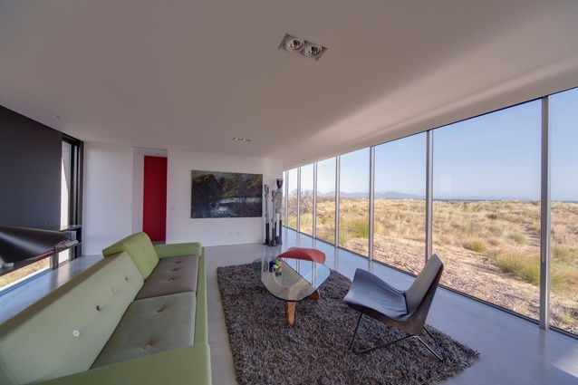 The large windows in the living space look out to the landscape.