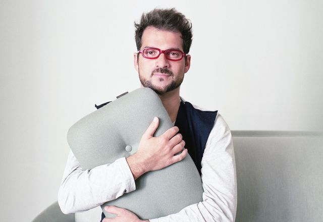 Jaime Hayón cuddles up to the Favn sofa, designed for Fritz Hansen.