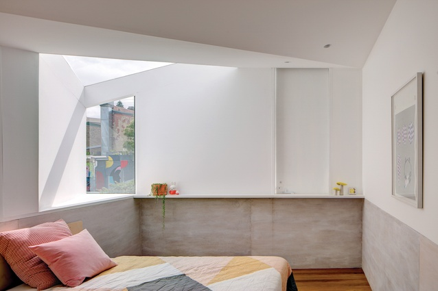 A splayed window and skylight in the corner of the rear bedroom expand the interior beyond its limited footprint. Artwork: Mark Whalen.