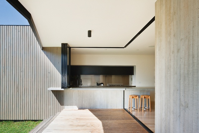 The kitchen bench is partially exposed on the outside, allowing for a connection between indoor and outdoor spaces and activities.