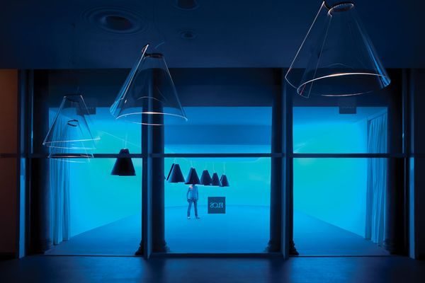 The space is serene and awash with a blue light, with cones hanging at different heights.