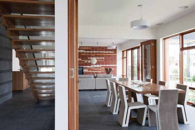 Living spaces face north, while services are on the southern edge. The dining room table was created from recycled timber from the original Waverley Park stadium.