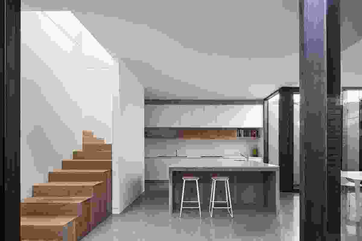 The ground-floor kitchen and living area are structured as a series of zones within a larger volume.
