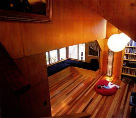 The view down the stairs into the living area, with its mixed hardwood floor.