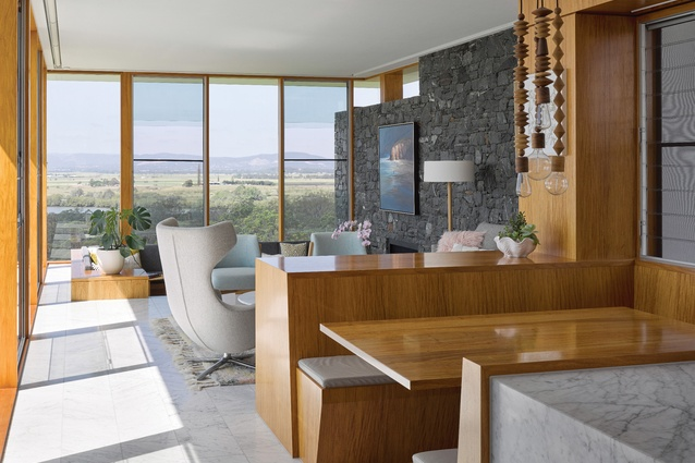 A dining nook and sunken lounge area within the southern wing reach out to distant views. Artwork: Mel Brigg.