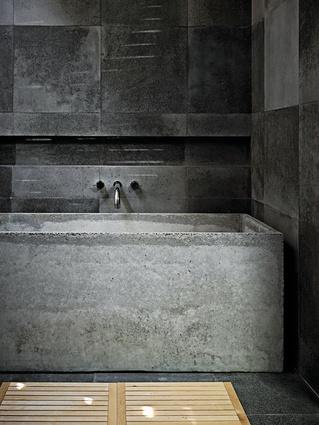 The bathroom features a custom-made concrete bath.
