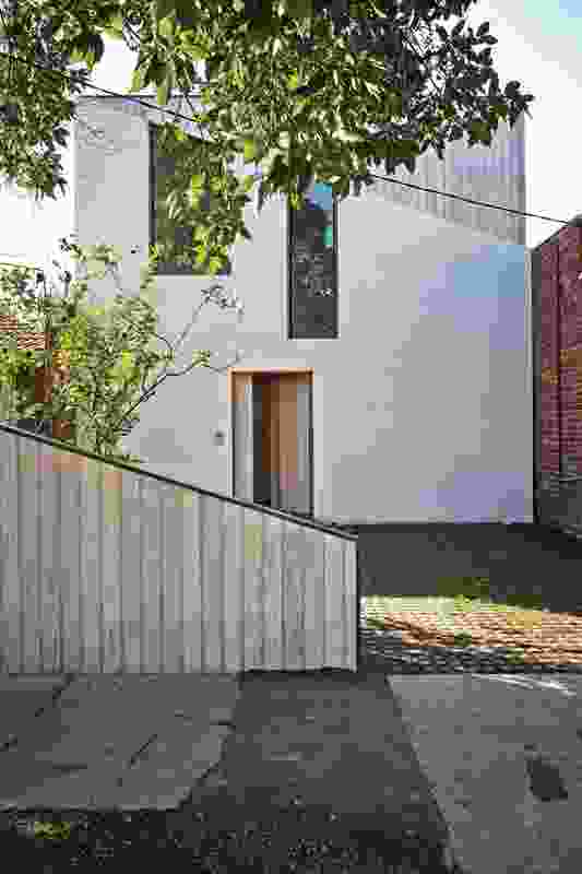 Timber and rendered block intertwine on the street elevation in a clever diagram of the project.