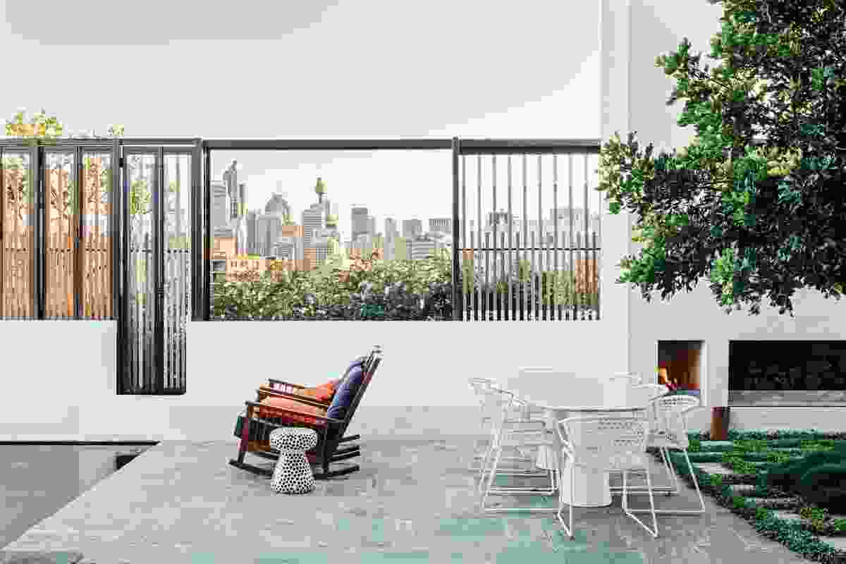A patio area adjacent to a pool and skirted by greenery offers stunning views of the city.