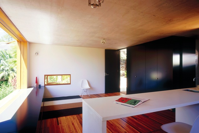 The pared-back interior of the studio space comprises exposed concrete, recycled blackbutt and a combination of painted and stained wall and door surfaces.
