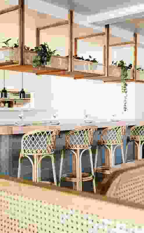 Rattan furniture and soft green tiles reference a sense of nostalgia for coastal holidays.