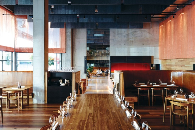 The double-height restaurant features a suspended industrial copper mesh curtain.