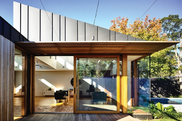 The new addition is capped with two north-facing sawtooth highlight windows that funnel light into the main living area.