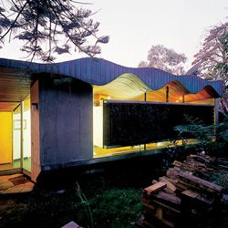 """Looking along the bush facade, with undulating roof and """"floating"""" concrete wall panel."""