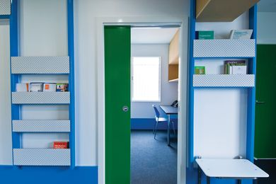 Bright blue and green against white and raw MDF sets an upbeat tone.