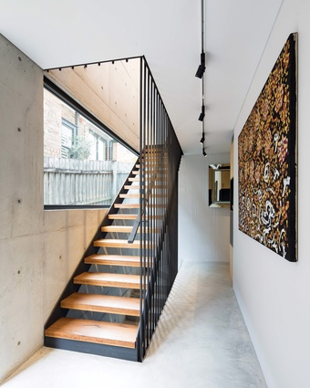 """The black steel staircase """"glints and glistens"""" when it catches the light coming through the large picture window. Artwork: Johnny Warangkula Tjupurrula."""