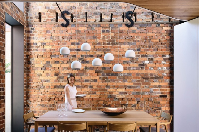 A volley of white pendant lights descends through the void, becoming a sculptural feature.