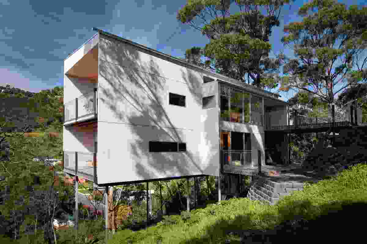 A regular grid of unpainted cement sheets forms the external shell of House 14A. The steepness of the site means that each house has a minimal footprint.