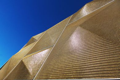 Bronze pyramids to the facade screen glow in direct sunlight: the mesh provides good visibility to those working inside.