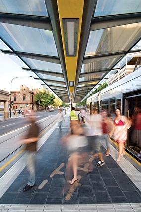 Moving through the city: people alight from a tram at one of central Adelaide's tram stops. The stops were designed by Peter Elliott Architecture and Urban Design, Dryden Crute Design and TCL.