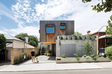 The interplay of Australian cypress and off-form concrete contributes to a contextually sympathetic facade.