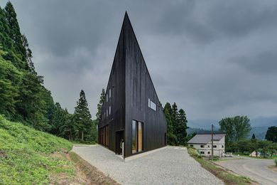 The dark, striking roof form serves a snow-shedding function.