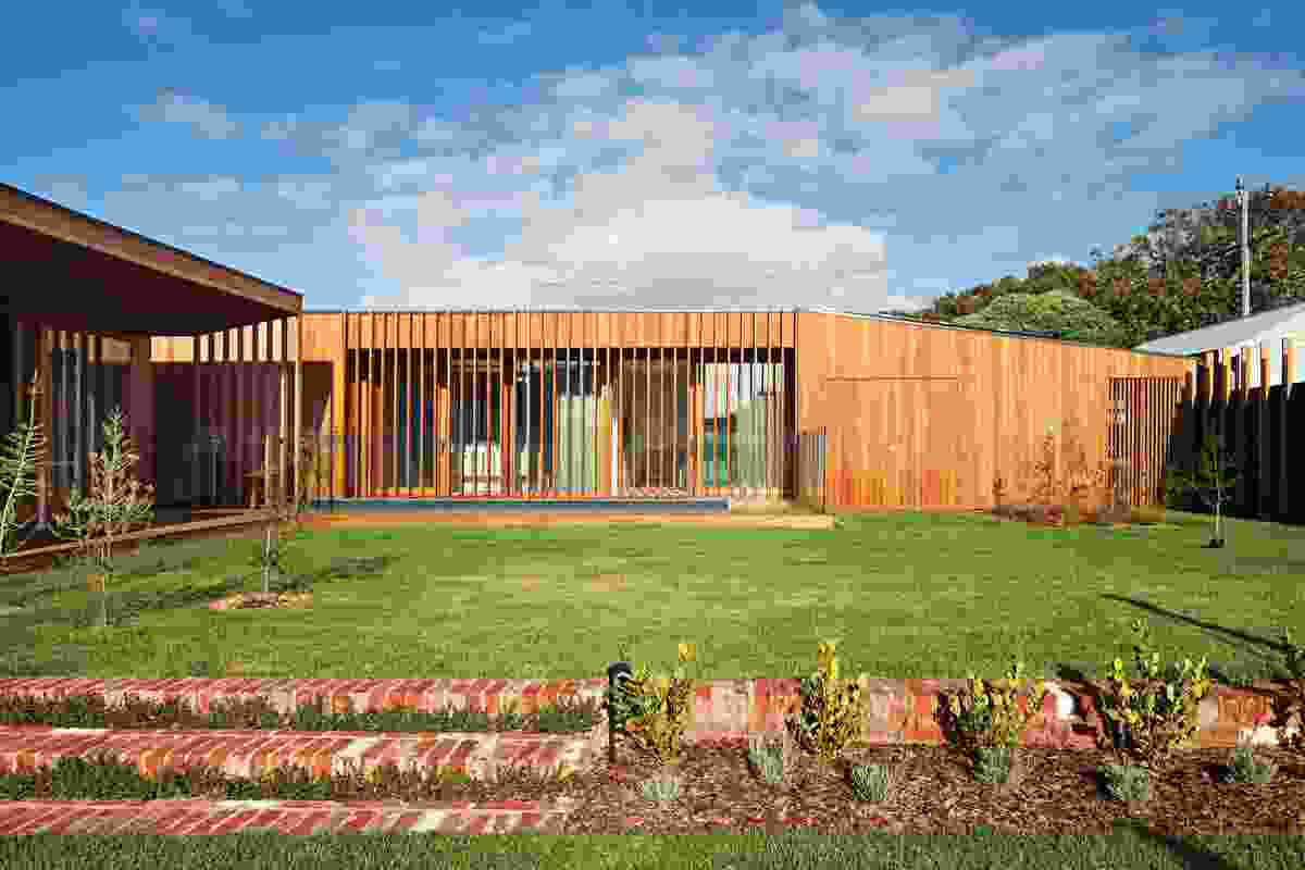 The house's L-shaped plan forms a protective perimeter around a private lawn and garden.