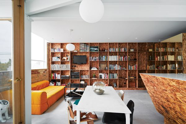 The southern wall is lined with a floor-to-ceiling bookshelf that matches the kitchen joinery.