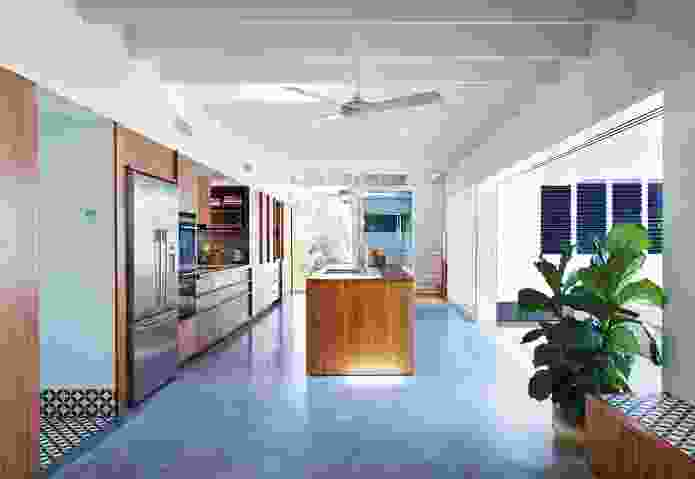 The kitchen's polished concrete floor opens out to the backyard through stacking sliding doors.