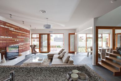 Recycled bricks are artfully arranged to demonstrate the reverse-brick veneer construction as a feature in the living room.