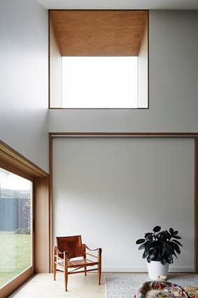 Deep-set cedar-framed windows punctuate the clean plasterboard surfaces and frame views of the landscape.