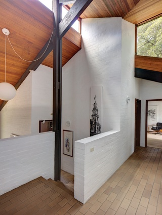 The interior features exposed structural elements and materials such as black-stained timber roof beams, spotted gum ceilings and whitewashed walls.