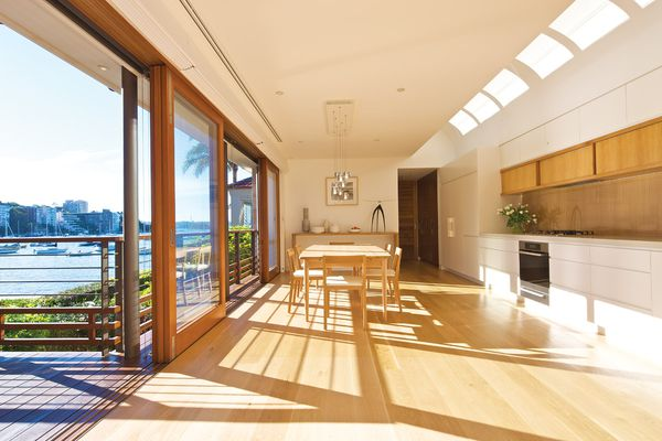 The kitchen and dining area overlooks a harbour beach in Sydney.
