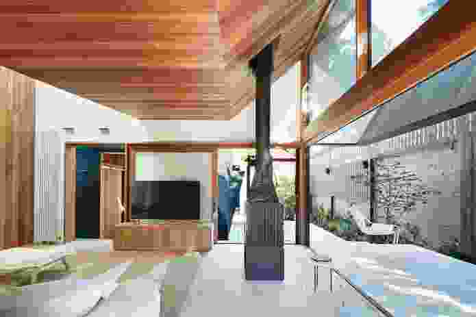 The rear of the addition opens out to the garden through sliding doors, with the distinctive roof hovering overhead.