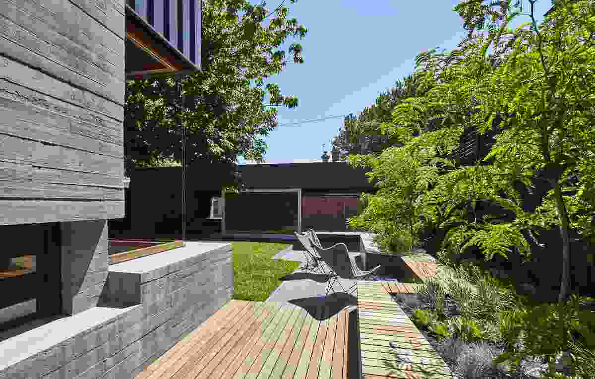 An inbuilt concrete seat wraps around a raised garden bed and extends to make a connection with the rear garage/studio.