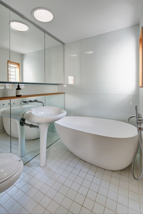 The white palette, mirrors and curved bathroomware help the small bathroom to feel more spacious than it is.