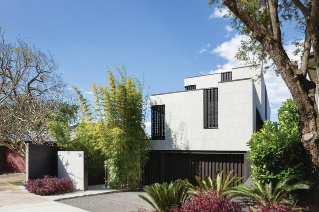 """From the street, the dwelling has a """"ziggurat form,"""" with asymmetric fenestration on each level screened by zigzagging perforated metal panels."""