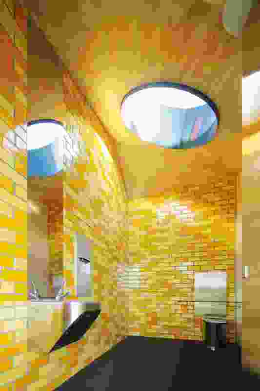 Brightly coloured glazed bricks, plywood ceilings and large circular skylights lend the facilities an air of exuberance.