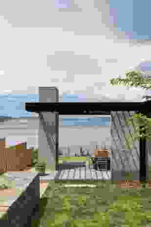 To the north, an outdoor room is framed by a concrete block fireplace and a pergola overhead.