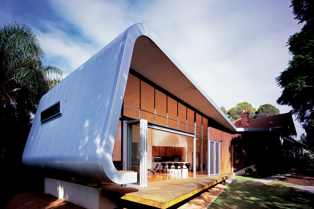 The extension is grafted onto the rear of an early-twentieth-century brick bungalow.