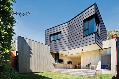The first-floor addition clad vertically in glazed concrete roof tiles.