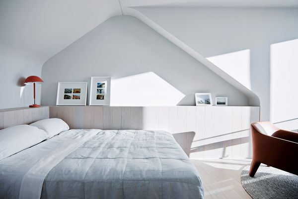 A recessed niche in the bedroom wall makes reference to the form of the original attic space.