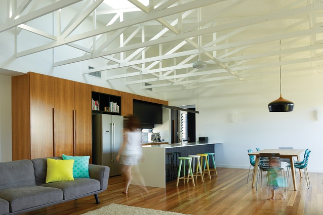 Exposed trusses are painted white, adding subtle texture to the open-plan kitchen/ living/dining area.