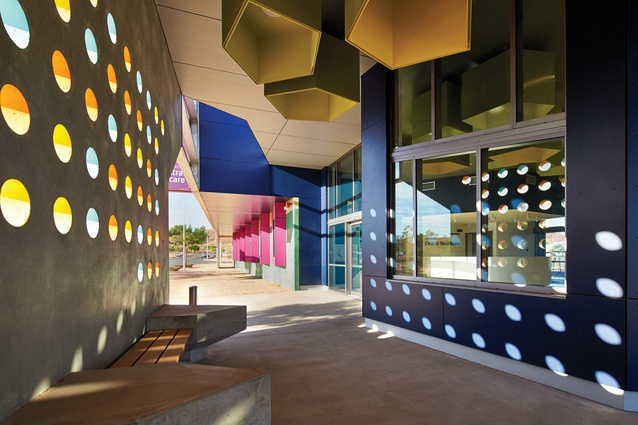 Perforations in the precast concrete verandah panels create patterns of light and shadow on the exterior walls and floor of the central waiting area.