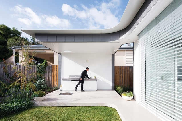 The roof and floor planes of the rear pavilion curve gently around to form a barbecue area.