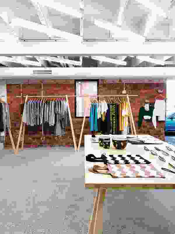 Concrete floors and exposed brick mark the space as a blank background for the clothes.